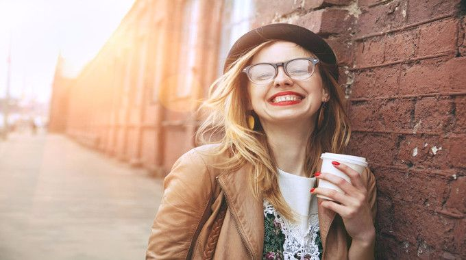 Woman smiling with a cup of coffee-compressed