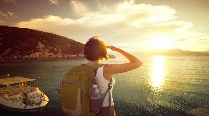 woman-hiker-standing-on-the-coast-and-enjoying-sunrise-over-the-sea-compressed